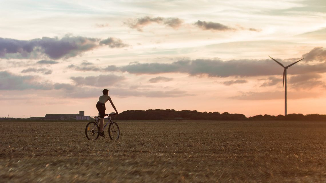man cycling near wind mill